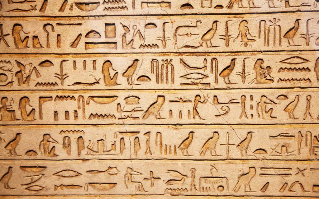 """Hieróglifos egípcios. Hieróglifo é um termo originário de duas palavras gregas: ἱερός (hierós) """"sagrado"""", e γλύφειν (glýphein) """"escrita"""". Apenas os sacerdotes, membros da realeza, altos cargos, e escribas conheciam a arte de ler e escrever esses sinais """"sagrados""""."""