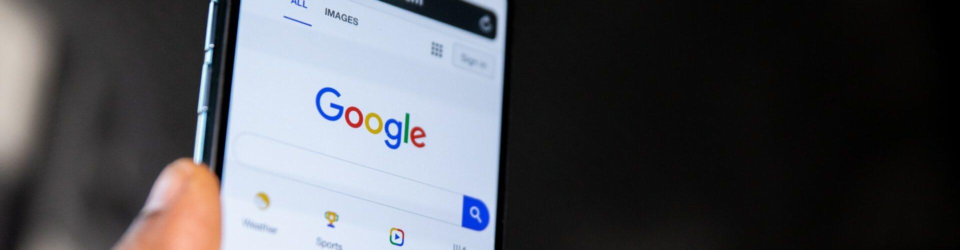 Mão segura smartphone no Google